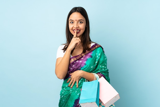 Femme indienne avec des sacs montrant un signe de silence geste mettant le doigt dans la bouche
