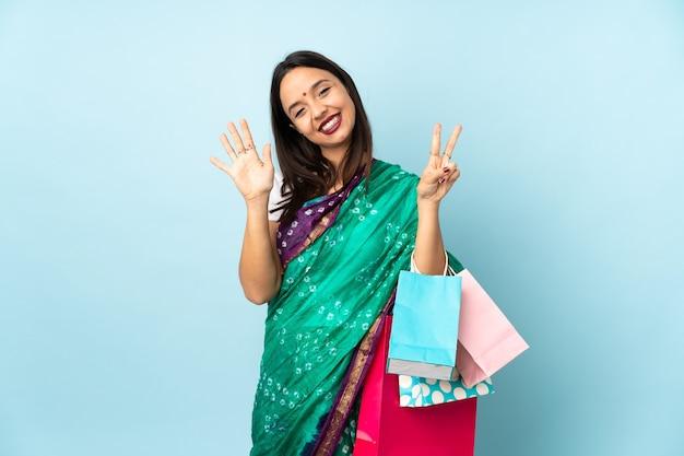 Femme indienne avec des sacs à provisions comptant sept avec les doigts