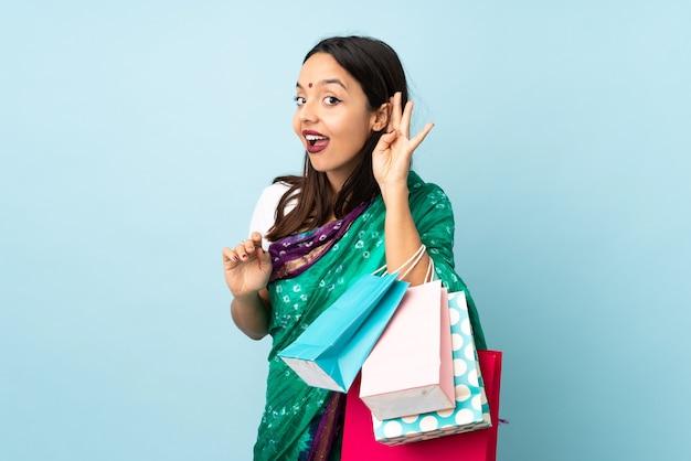 Femme indienne avec des sacs à provisions, écouter quelque chose