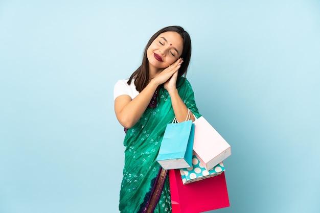 Femme indienne avec des sacs à provisions faisant le geste de sommeil dans une expression dorable