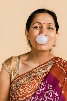 Femme indienne senior dans un sari traditionnel soufflant une bulle avec un chewing-gum