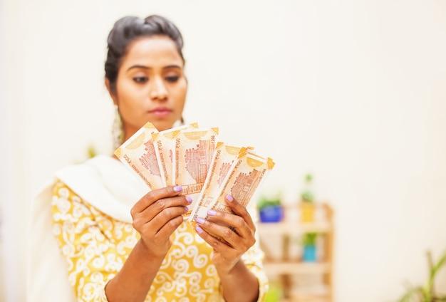 Femme indienne sérieuse inquiète comptant de l'argent en roupies indiennes à la maison