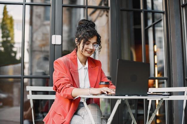 Femme indienne travaillant sur un ordinateur portable dans un café de la rue. porter des vêtements élégants et élégants - veste, lunettes