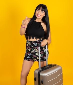 Femme indienne avec valise de voyage espace jaune