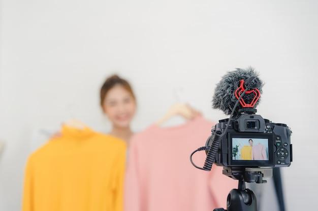 Femme influente en ligne de blogueuse mode asiatique tenant des sacs à provisions et beaucoup de vêtements