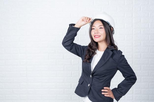 Femme d'ingénierie tenant un chapeau, séparer le mur de briques blanches fait des gestes avec la langue des signes.