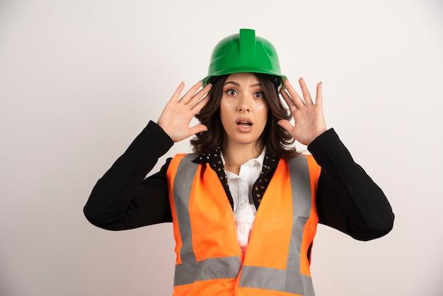 Femme ingénieur agissant surpris sur blanc