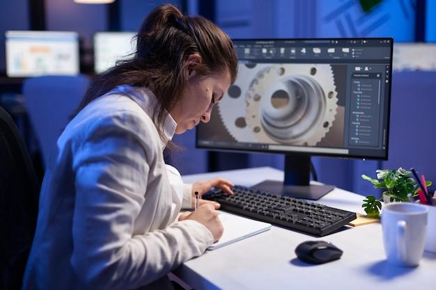 Femme ingénieur architecte travaillant dans un programme de cao moderne assis au bureau dans un bureau d'entreprise en démarrage. un employé industriel lance une nouvelle idée de prototype sur ordinateur à l'aide d'un concept de design innovant