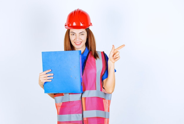 Femme Ingénieur En Casque Rouge Tenant Un Dossier De Projet Bleu Et Présentant Quelqu'un Ou Quelque Chose. Photo gratuit