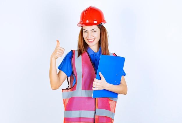 Femme ingénieur en casque rouge tenant un dossier de projet bleu et se sentant puissante et positive.
