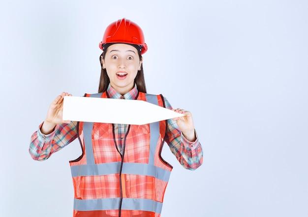 Femme ingénieur en casque rouge tenant une flèche pointant vers la droite.