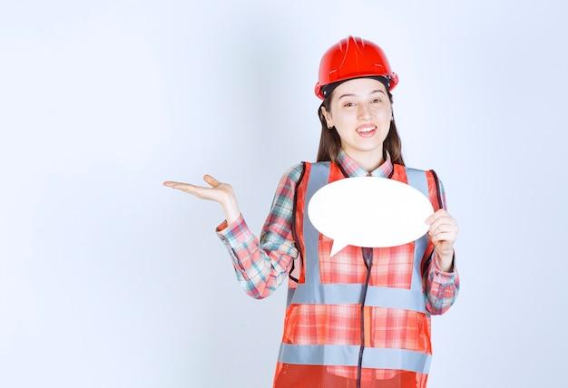Femme ingénieur en casque rouge tenant un panneau d'information ovale.