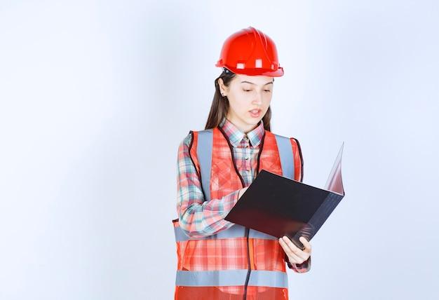 Femme ingénieur en casque rouge tenant un plan de projet noir.