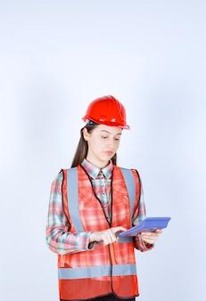 Femme ingénieur en casque rouge travaillant sur calculatrice.
