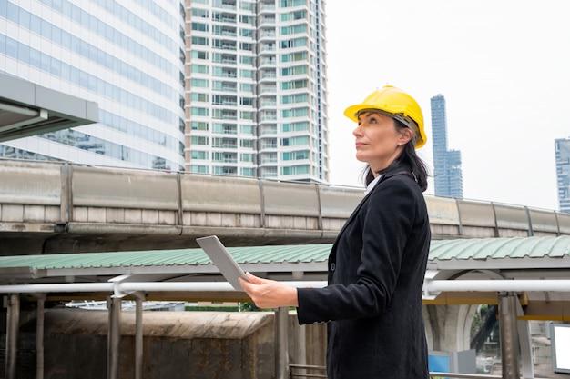 Femme, ingénieur, à, casque, stand, tenue, ordinateur portable, sur, ciel, train, urbain