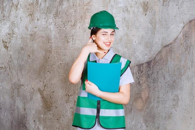 Femme ingénieur en casque vert tenant un dossier bleu