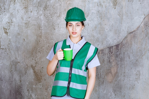 Femme ingénieur en casque vert tenant une tasse de café vert