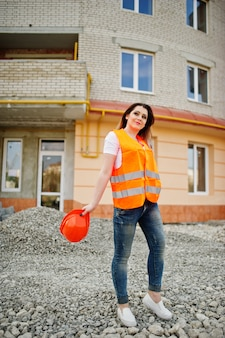 Femme ingénieur constructeur en uniforme gilet et casque de protection orange contre le nouveau bâtiment