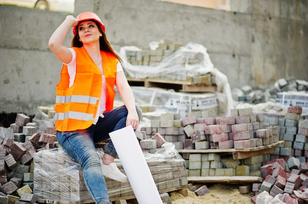 Femme ingénieur constructeur en uniforme gilet et casque de protection orange tenir papier plan de mise en page des affaires assis sur le trottoir.