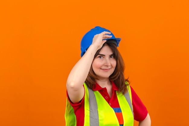 Femme ingénieur en gilet de construction et casque de sécurité à la confiance faisant geste de salutation touchant le casque sur mur orange isolé