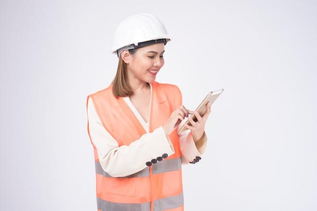Une femme ingénieur portant un casque de protection sur fond blanc studio