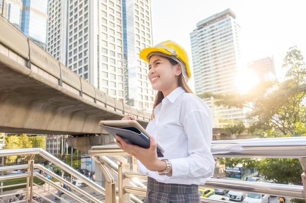Femme d'ingénieur travaille dans le contexte de la ville en plein air