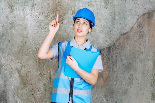 Femme ingénieur en uniforme bleu et casque tenant un dossier de rapport bleu et pointant vers quelqu'un autour.