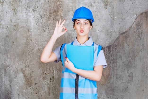 Femme ingénieur en uniforme bleu et casque tenant un dossier de rapport bleu.