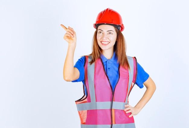Femme ingénieur en uniforme et casque rouge montrant le côté gauche.
