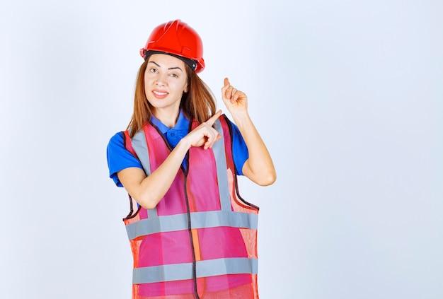 Femme ingénieur en uniforme et casque rouge montrant quelque chose derrière.