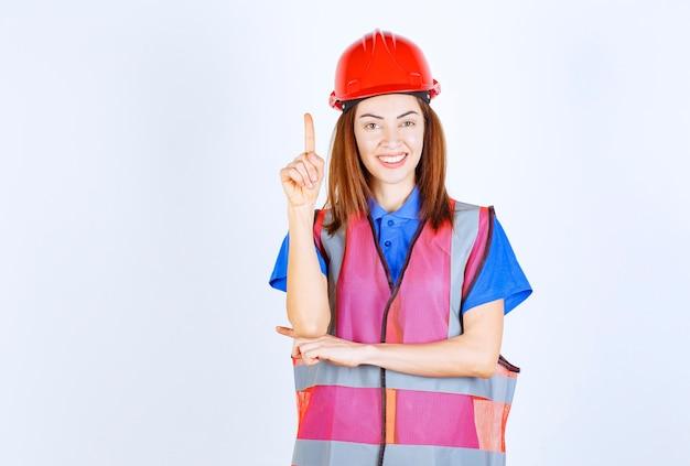 Femme ingénieur en uniforme et casque rouge montrant quelque chose.