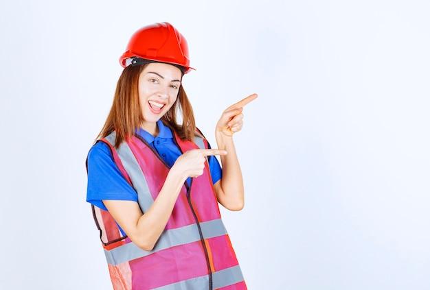 Femme ingénieur en uniforme et casque rouge pointant vers quelqu'un sur la droite.