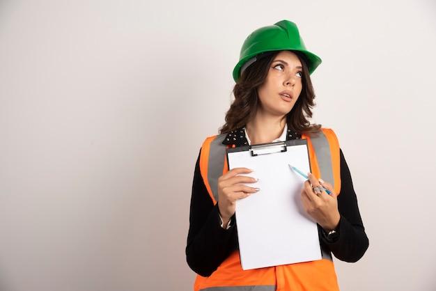 Femme ingénieur en uniforme de sécurité pointant sur des documents