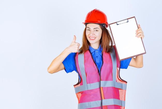 Femme ingénieur en uniforme tenant un fichier de rapport vierge et montrant un signe de satisfaction.