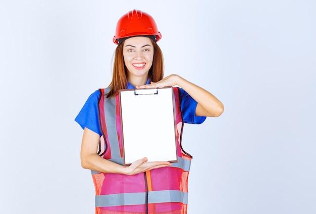 Femme ingénieur en uniforme tenant un fichier de rapport vierge.