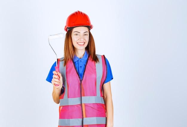 Femme ingénieur en uniforme tenant un rouleau de peinture de couleur blanche.