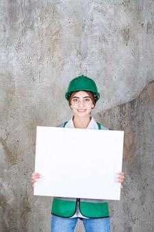 Femme ingénieur en uniforme vert et casque tenant un panneau d'information rectangle.