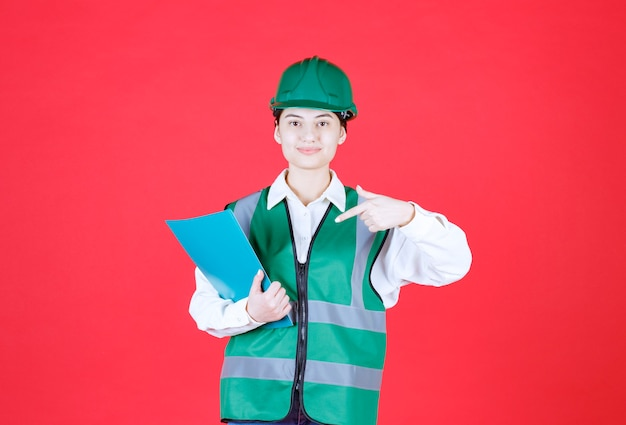 Femme ingénieur en uniforme vert tenant un dossier bleu