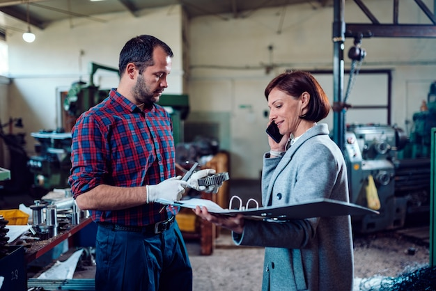 Femme ingénieure debout avec machiniste et parlant au téléphone avec le client