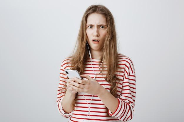 Une femme inquiète et choquée regarde inquiète après avoir lu un message étrange sur un téléphone mobile