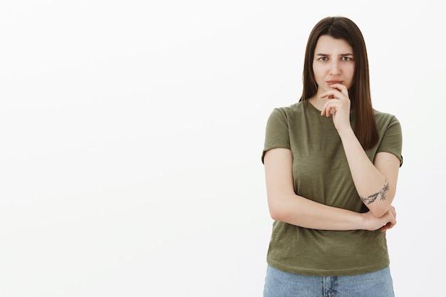 Femme inquiète et hésitante en entendant quelque chose de dérangeant, fronçant les sourcils d'inquiétude et de désapprobation intense tenant la main sur la lèvre, considérant ce que faire, debout réfléchie et incertaine sur un mur gris