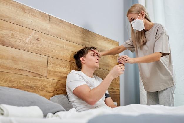 Une femme inquiète prend soin de son mari malade alors qu'elle est assise sur un lit à la maison pour vérifier la température, les gens doivent porter un masque médical protégeant de la pandémie de coronavirus covid-19, mis en quarantaine