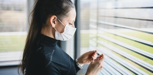 Femme inquiète souffrante avec thermomètre et masques faciaux à l'intérieur à la maison, concept de virus corona.