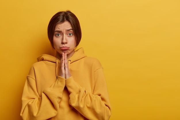 Une femme insatisfaite a foi en mieux, tient la main pour prier, demande grâce, a une expression triste, supplie et anticipe quelque chose