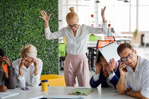 Une femme insatisfaite a perdu son sang-froid à cause de la colère au travail, crie à cause du mauvais travail et du résultat, les employés sont humiliés