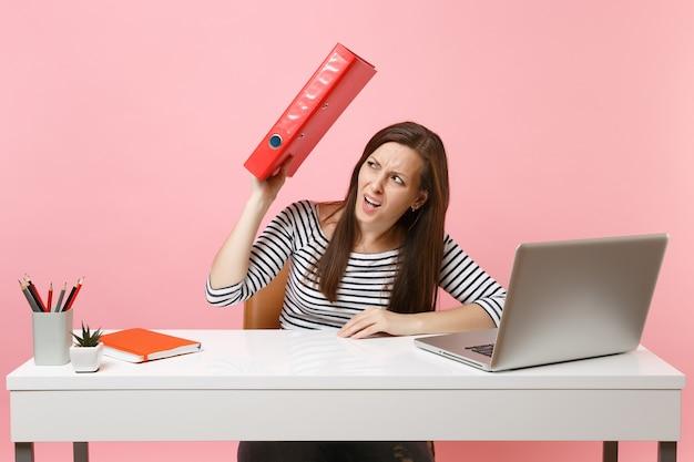 Femme insatisfaite se cachant derrière un dossier rouge avec un document papier travaillant sur un projet tout en étant assise au bureau avec un ordinateur portable
