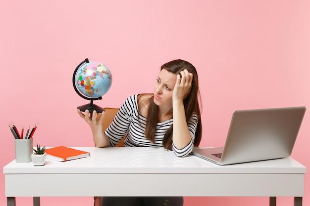 Une femme insatisfaite se penche sur la main tenant un globe ayant des problèmes avec la planification des vacances tout en étant assise, travaille au bureau avec un ordinateur portable