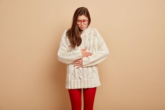 Une femme insatisfaite souffre de maux de ventre, garde les mains sur le ventre, ressent des crampes, a très faim, a une expression triste