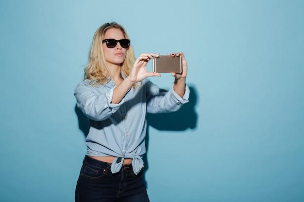 Femme insouciante en chemise et lunettes de soleil faisant selfie sur smartphone