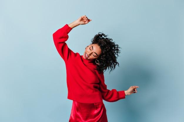 Femme insouciante dans la danse rouge totale et agitant les mains